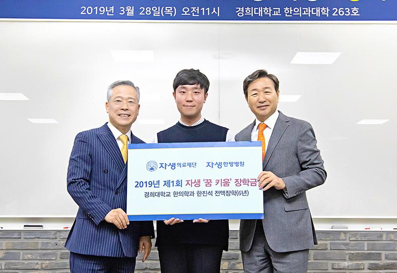 [사진설명] 자생의료재단 신준식 명예이사장(오른쪽)이 자생 꿈키움 장학생 한진석 군(가운데)에게 장학금을 전달하고 있다