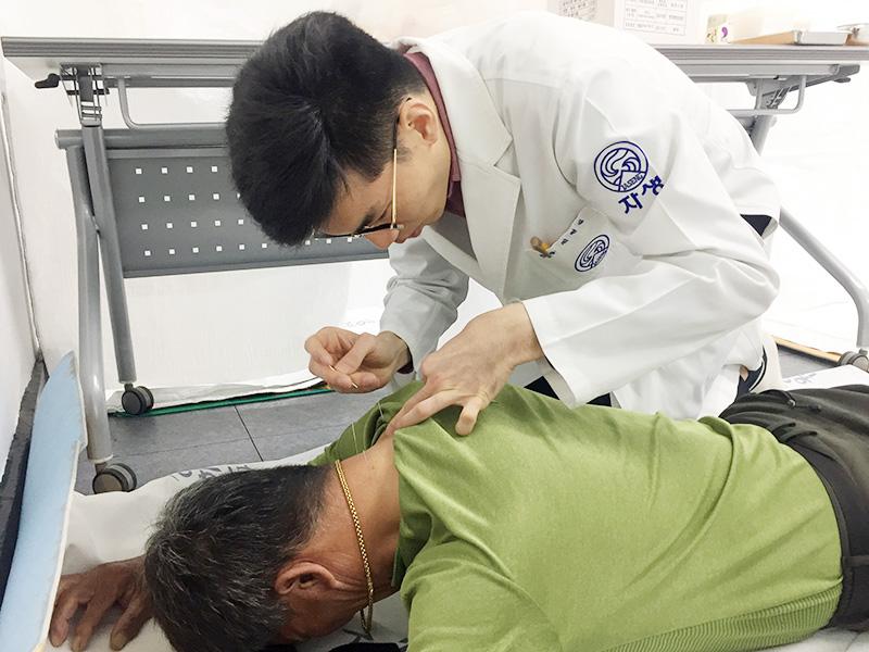 [사진설명] 창원자생한방병원 의료진이 진료소를 찾은 고령 농민에게 침치료를 실시하고 있다 - 자생의료재단ㆍ자생한방병원