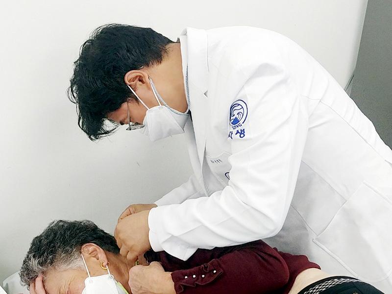잠실자생한방병원 신민식 병원장이 지역 노인에게 침 치료를 실시하고 있다. | 자생한방병원·자생의료재단