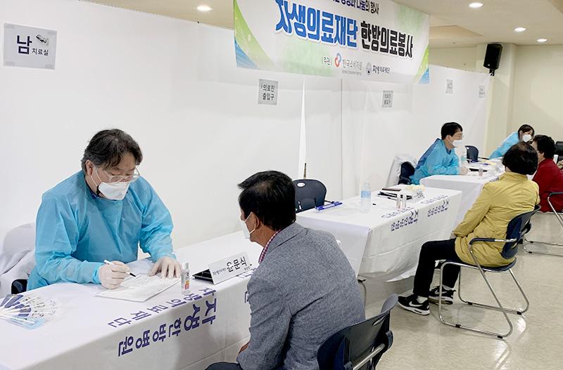 수원자생한방병원 윤문식 병원장(왼쪽)이 어르신과 건강상담을 하고 있다.   자생한방병원·자생의료재단