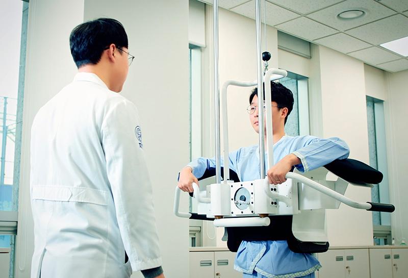 동작침법 원리에 착안한 치료 기구로 환자를 치료 중인 자생한방병원 의료진의 모습   자생한방병원
