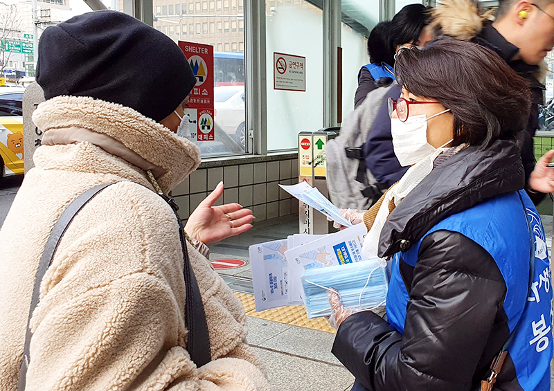 강남자생봉사단원이 시민에게 마스크를 전달하고 신종 코로나바이러스 감염증 예방법을 설명하고 있다