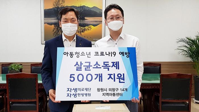 [사진설명] 창원자생한방병원 강인 병원장(오른쪽)이 창원시 의창구청 홍명표 구청장(왼쪽)에게 손소독제 500개를 기부하고 있다