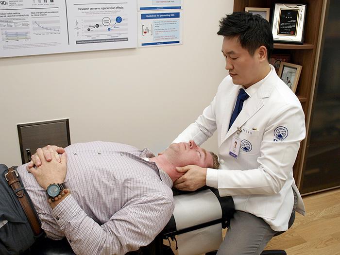 자생한방병원 김하늘 국제진료센터장이 보건의료전문가 연수단 중 한 명에게 추나요법을 실시하고 있다